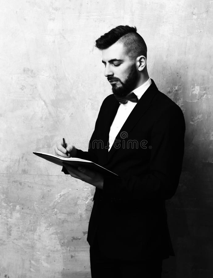 Piani barbuti dell'uomo d'affari Il dirigente alla moda con la barba ed il taglio di capelli moderno in costume classico scrive i fotografia stock libera da diritti