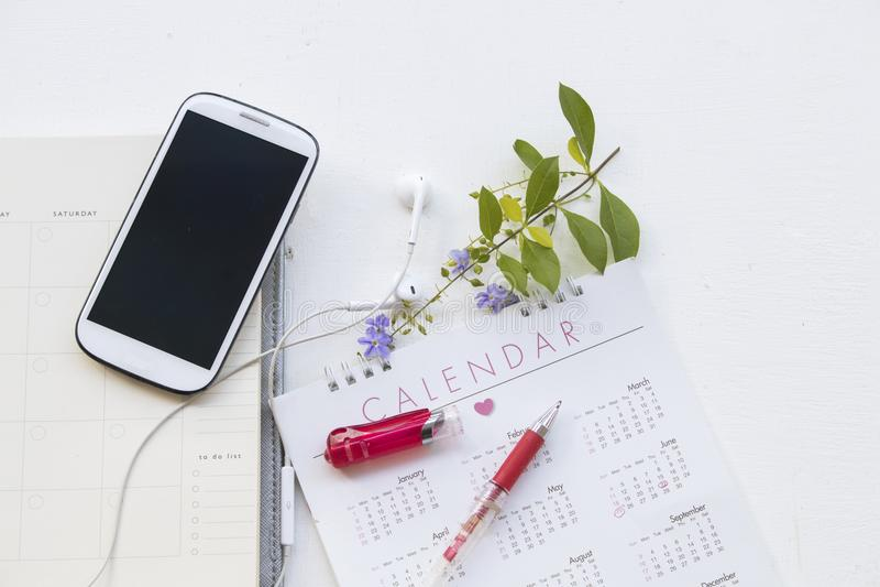 Pianificatore del taccuino con il calendario e telefono cellulare per l'affare immagini stock