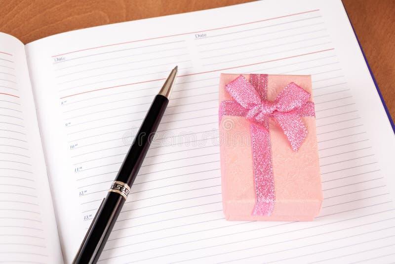Pianificatore personale con il contenitore e la penna di regalo fotografia stock