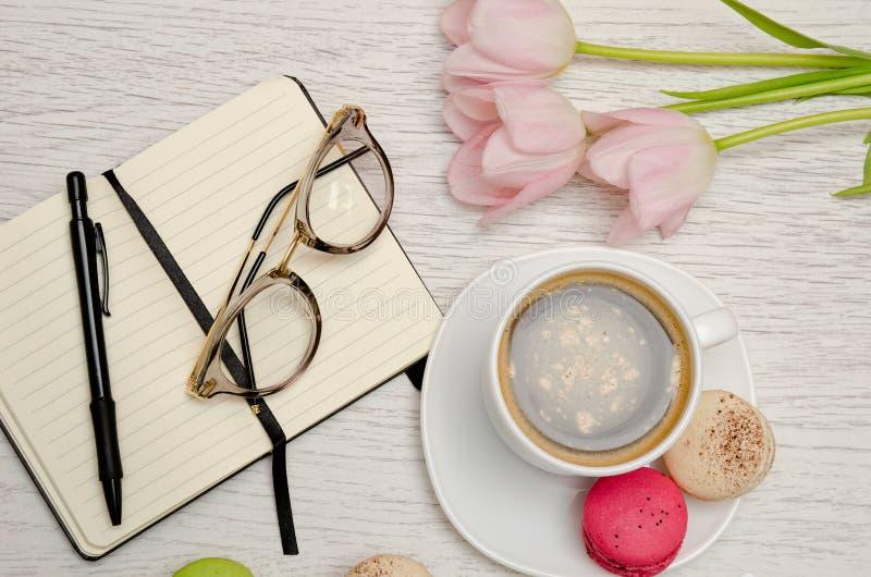 Pianificazione degli affari Tazza da caffè con il dessert, il taccuino, la penna ed i vetri immagine stock libera da diritti