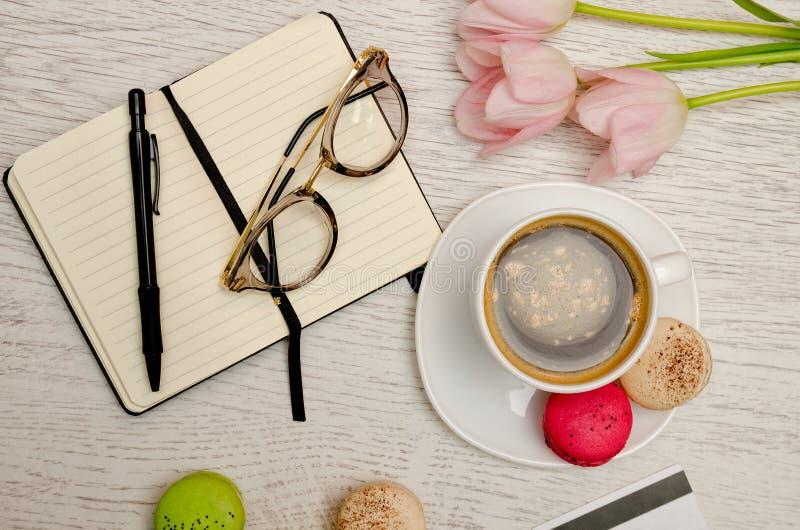 Pianificazione degli affari Tazza da caffè con il dessert, il taccuino, la penna ed i vetri immagini stock libere da diritti