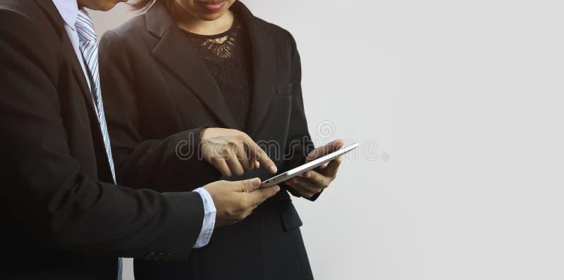 Pianificazione dell'uomo d'affari allo smartphone ed alla compressa con segretario e le donne di affari circa il progetto e la fi immagini stock