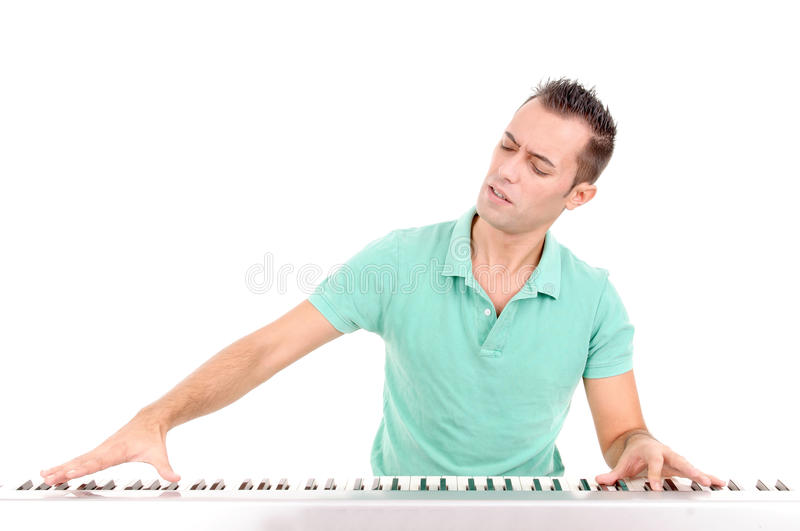 Pianist. Handsome young man playing the piano isolated in white background stock photo