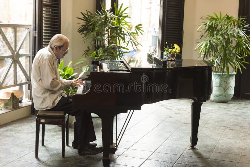 Pianista che gioca pianoforte a coda Avana immagini stock libere da diritti
