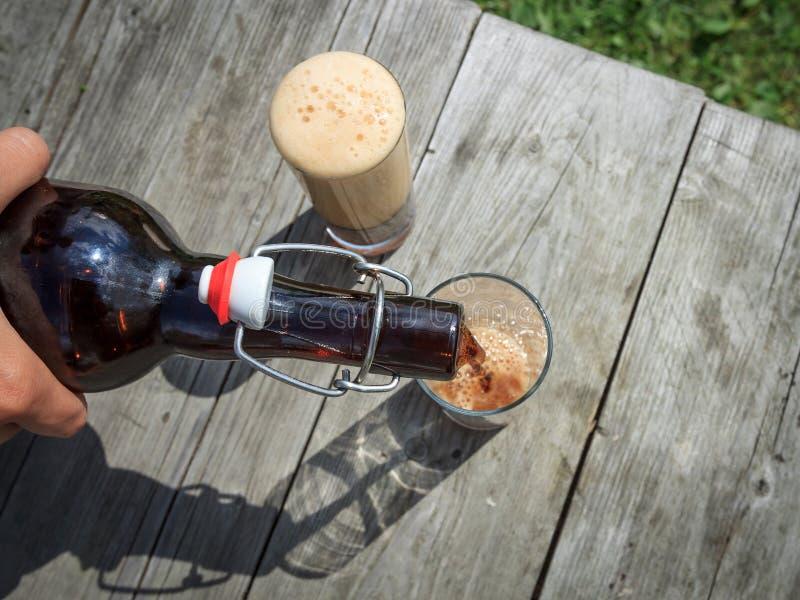 Piankowaty ciemnego piwa dolewanie w wysokich szkła od brown szklanej butelki w lato ogródzie na nieociosanym drewnianym stole fotografia stock