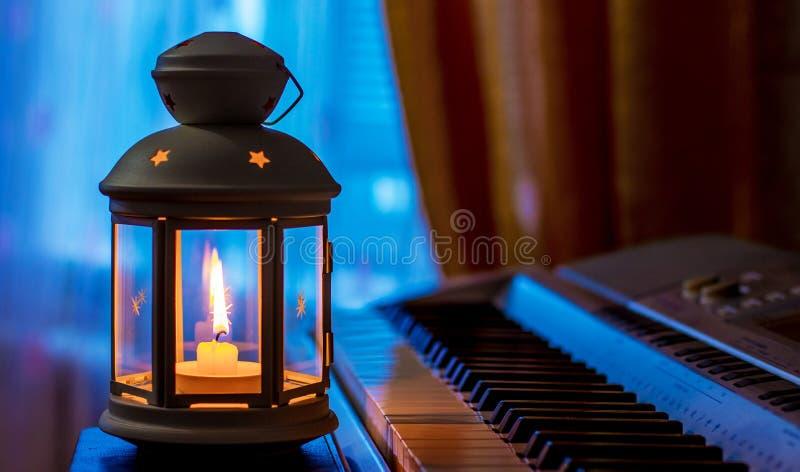 Piano à la lumière d'une lanterne avec une bougie Ex?cution de la musique avec le candles_ photographie stock