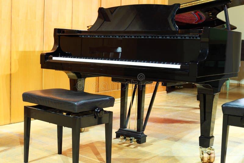 Piano à queue de concert et banc réglé dans le hall photo stock