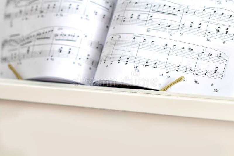 Piano bianco con le note del piano Fine in su fotografia stock libera da diritti