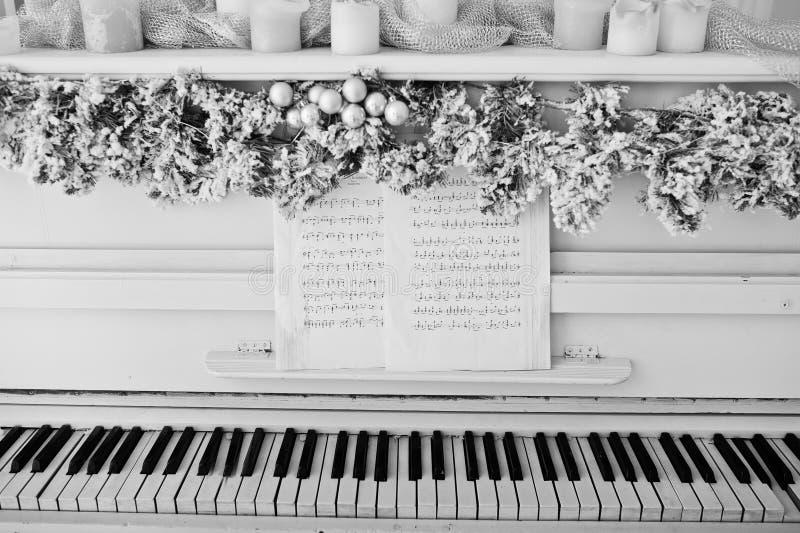 Piano blanc avec des bougies Concept heureux de vacances d'hiver photographie stock