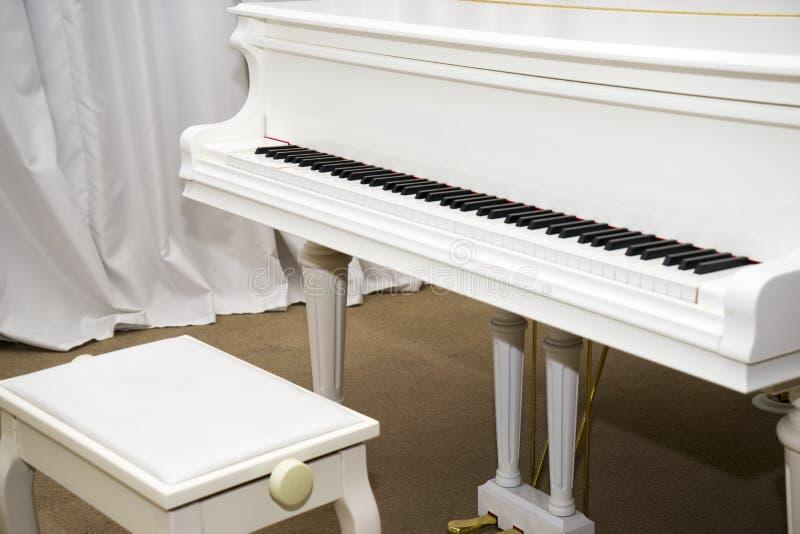 Piano blanco en la etapa de la sala de conciertos fotos de archivo libres de regalías
