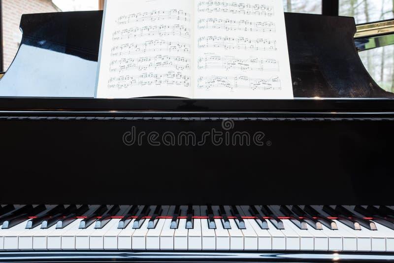 Piano clássico preto com livro de música imagem de stock