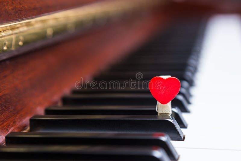 Piano con la clip di legno rossa del cuore immagini stock libere da diritti