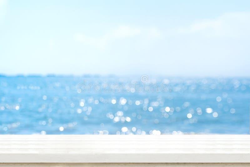 Piano d'appoggio di legno bianco della plancia vuota con il cielo blu della sfuocatura e il boek del mare fotografia stock libera da diritti