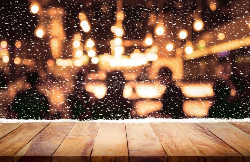 Piano d'appoggio di legno con le precipitazioni nevose e la gente nel fondo di inverno di notte immagine stock