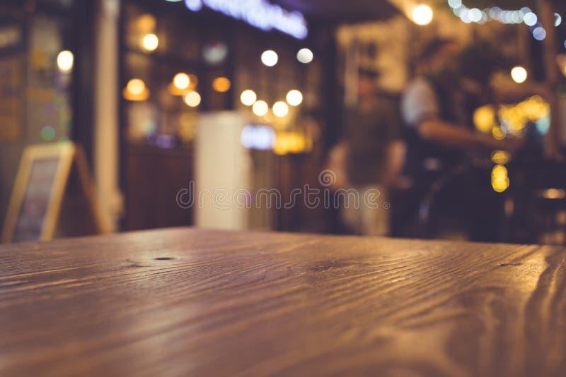 Piano d'appoggio di legno con sfuocatura di illuminazione nella comunità del ristorante del caffè di notte fotografia stock