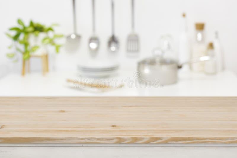 Piano d'appoggio di legno per l'esposizione del prodotto sul fondo vago della cucina fotografia stock