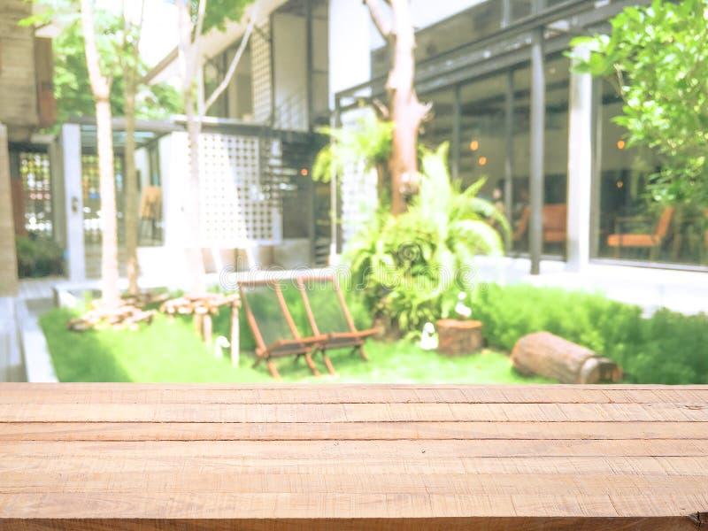 Piano d'appoggio di legno di pino con l'ingresso di lusso vago astratto dell'hotel del fondo ed il giardino verde fotografia stock libera da diritti