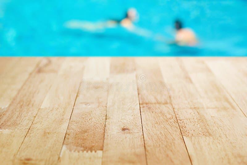 Piano d'appoggio di legno su fondo vago della piscina fotografia stock