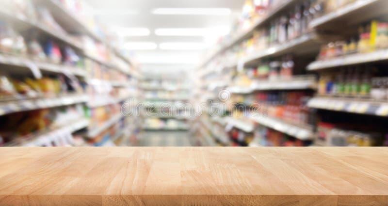 Piano d'appoggio di legno su sfuocatura del fondo dello scaffale del prodotto del supermercato fotografia stock