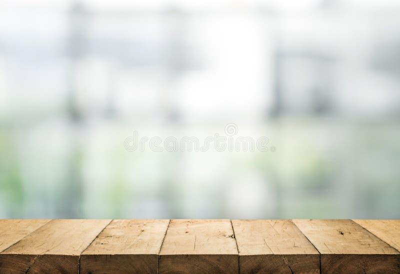 Piano d'appoggio di legno su sfuocatura del vetro di finestra astratto immagine stock libera da diritti