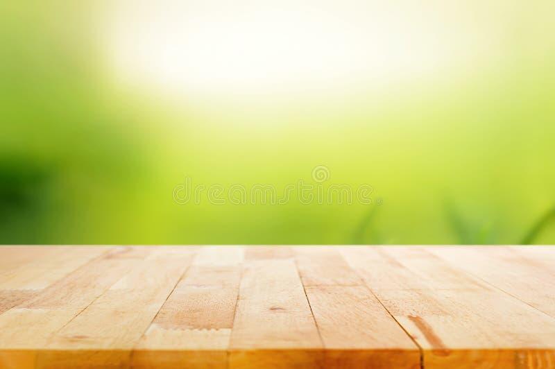 Piano d'appoggio di legno sul fondo astratto di verde della natura immagine stock libera da diritti