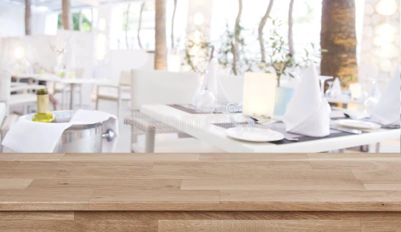 Piano d'appoggio di legno sul fondo defocused del ristorante con le tavole stabilite immagine stock