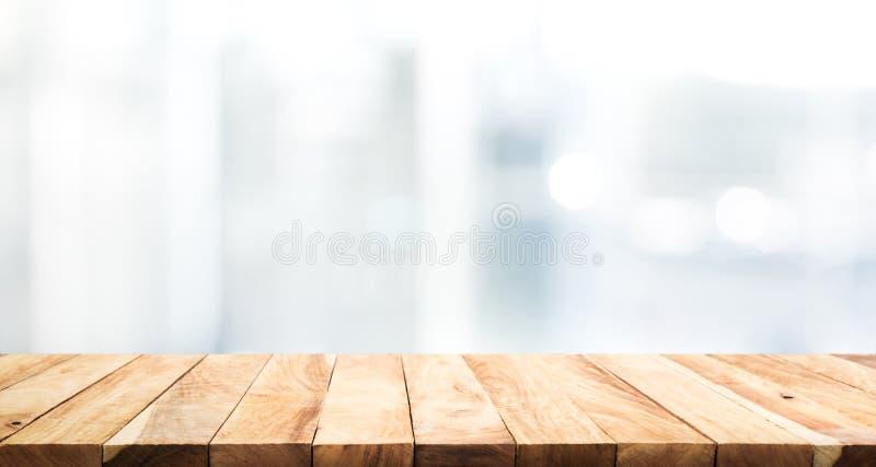 Piano d'appoggio di legno sul fondo della costruzione della parete della finestra di vetro della sfuocatura