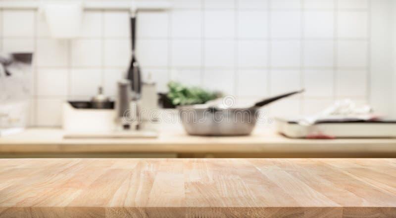 Piano d'appoggio di legno sul fondo della stanza della cucina della sfuocatura