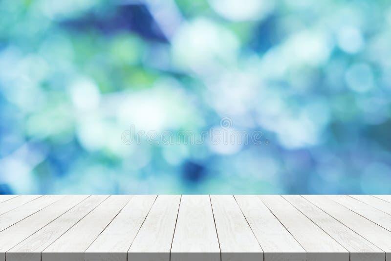 piano d'appoggio di legno sul fondo vago blu della natura per il montaggio il vostro prodotto immagini stock libere da diritti