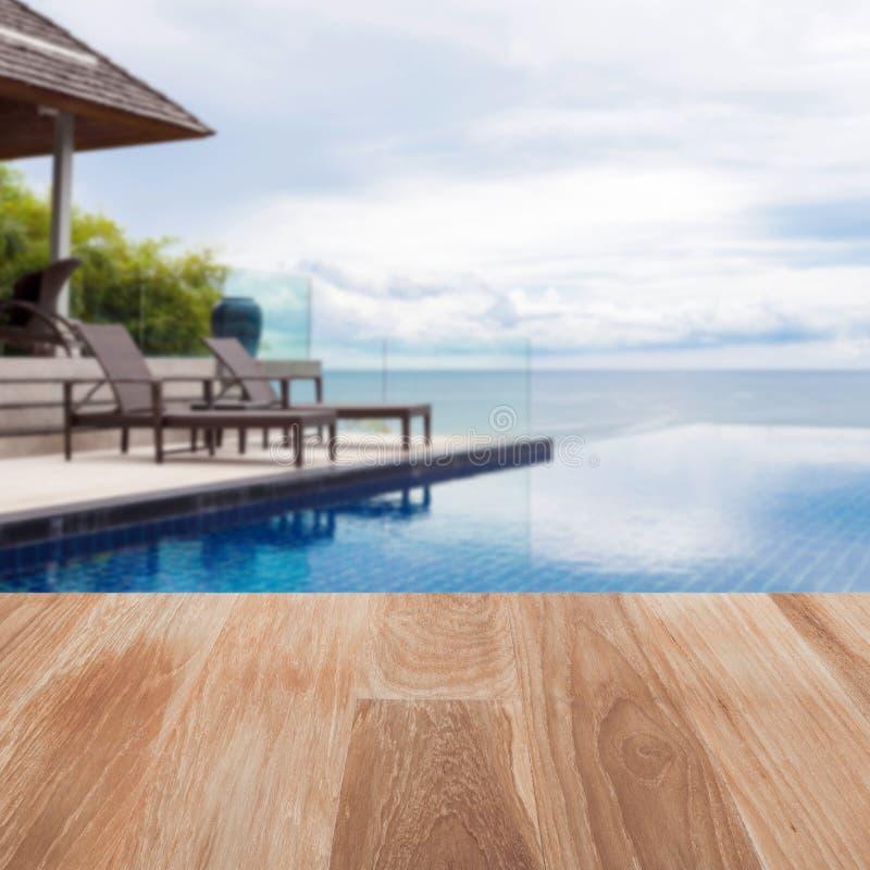 Piano d'appoggio di legno sulla sedia di spiaggia della sfuocatura in all'aperto con la piscina fotografia stock