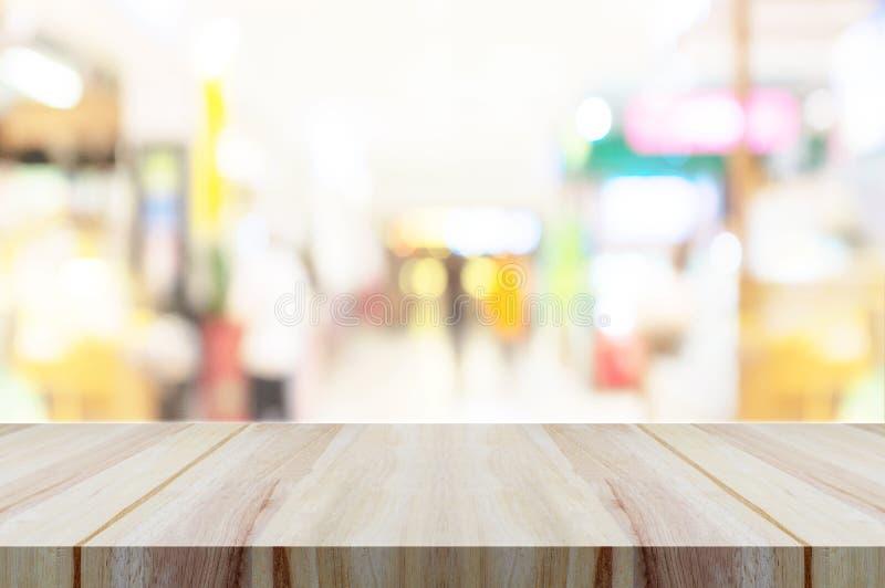 Piano d'appoggio di legno vuoto con il fondo moderno vago del centro commerciale sottragga la priorità bassa immagine stock libera da diritti