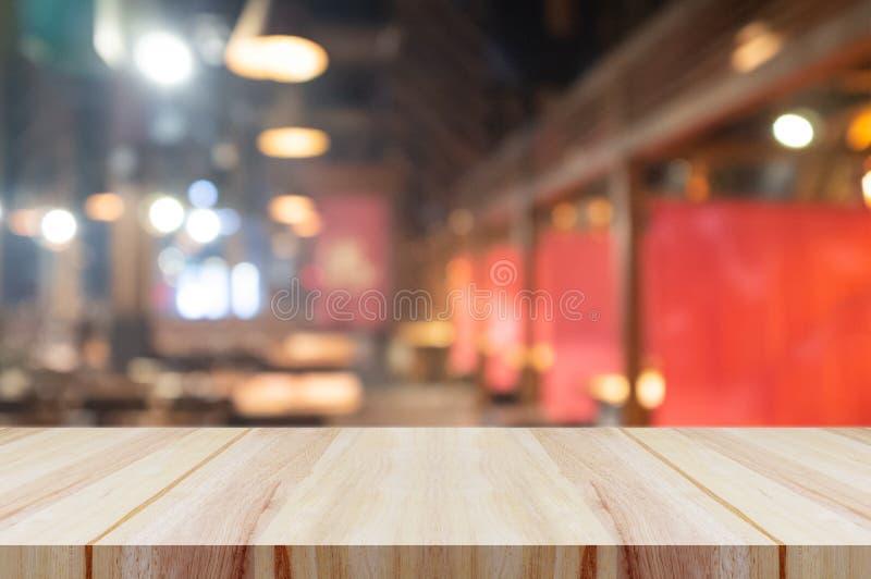 Piano d'appoggio di legno vuoto con il fondo vago dell'interno del ristorante o della caffetteria fotografie stock libere da diritti