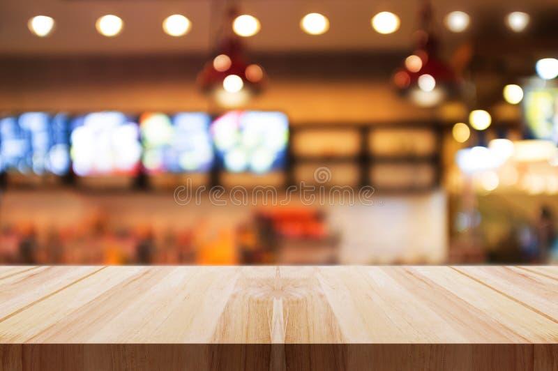 Piano d'appoggio di legno vuoto con il fondo vago dell'interno del ristorante o della caffetteria sottragga la priorità bassa immagini stock