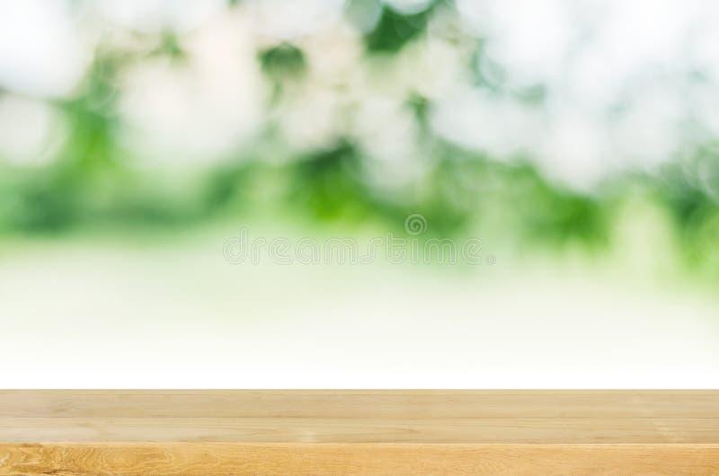 Piano d'appoggio di legno vuoto con il fondo verde vago del giardino fotografia stock