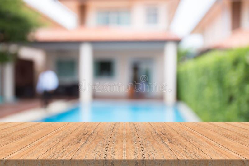 Piano d'appoggio di legno vuoto su fondo vago al giardino della piscina immagine stock libera da diritti