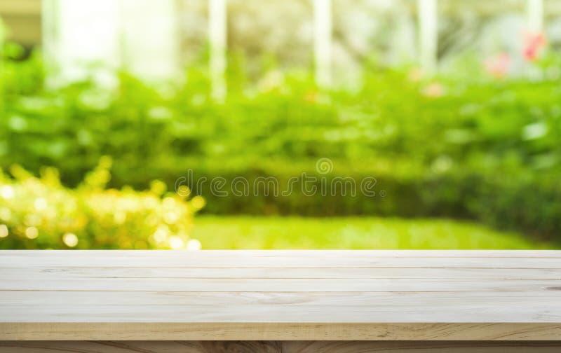 Piano d'appoggio di legno vuoto su verde del prato inglese dal giardino nella mattina immagini stock libere da diritti