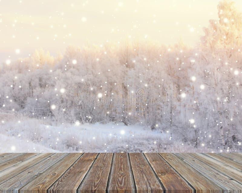 Piano d'appoggio di legno vuoto sul contesto vago di inverno con il fiocco di neve immagine stock libera da diritti