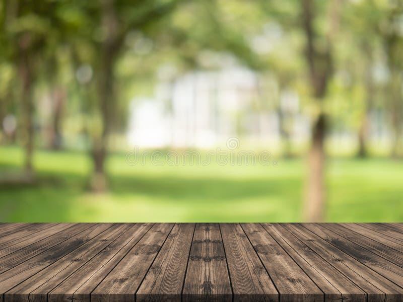 Piano d'appoggio di legno vuoto sul fondo vago verde della natura al giardino, spazio per il prodotto di manifestazione del monta fotografie stock libere da diritti
