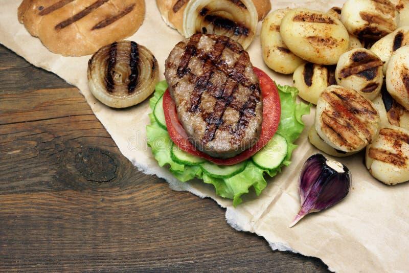 Piano d'appoggio di picnic con gli hamburger arrostiti e le verdure del BBQ fotografia stock