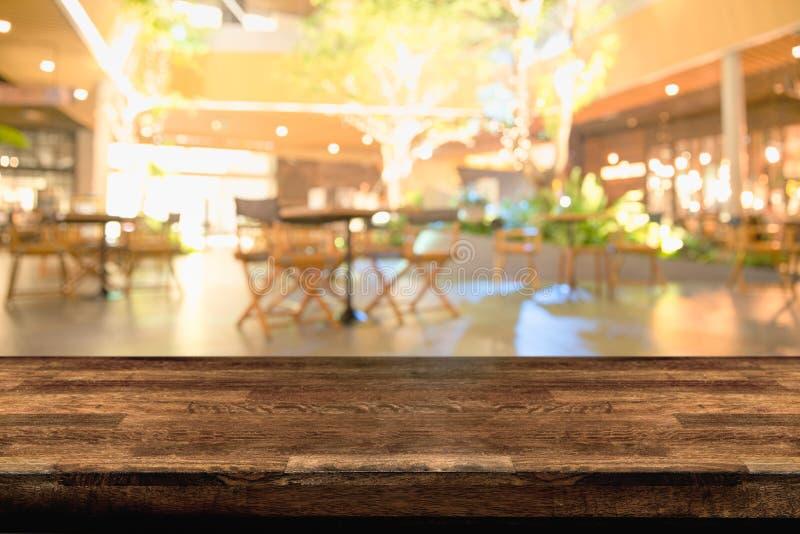Piano d'appoggio e sfuocatura di legno vuoti del fondo del pub o del ristorante di notte/di selettivo fotografie stock libere da diritti