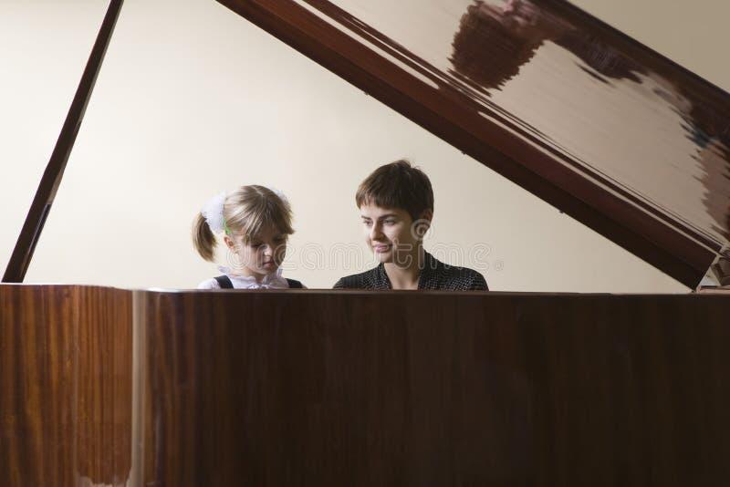 Piano d'And Teacher Playing d'étudiant photos libres de droits