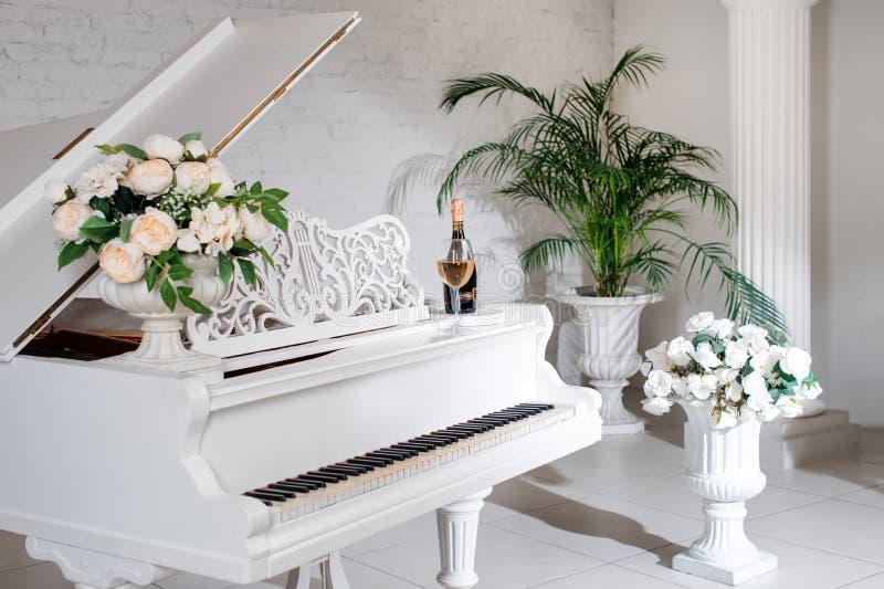 Piano de cola en un interior clásico blanco de lujo con el vino, las palmas y las flores fotos de archivo libres de regalías