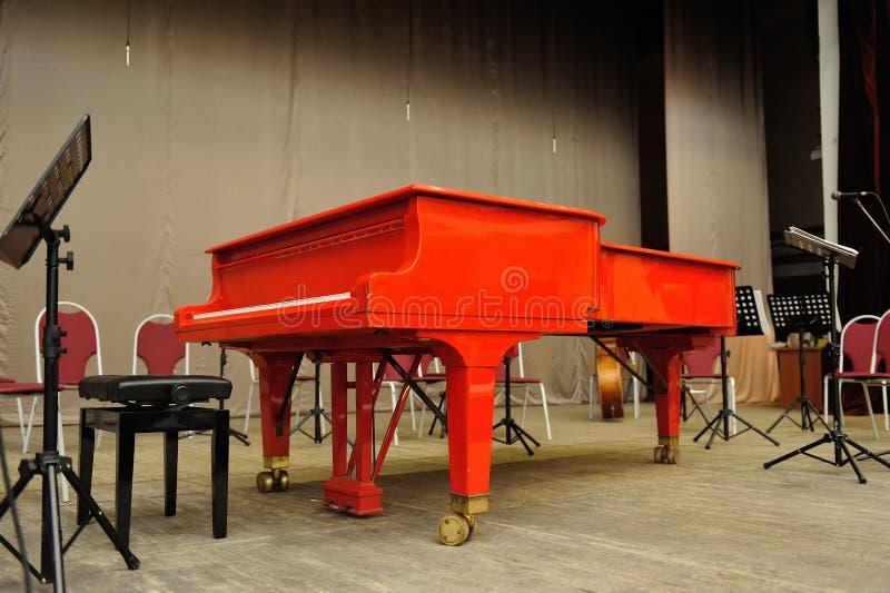 Piano de cola rojo en la sala de conciertos en etapa imagen de archivo libre de regalías