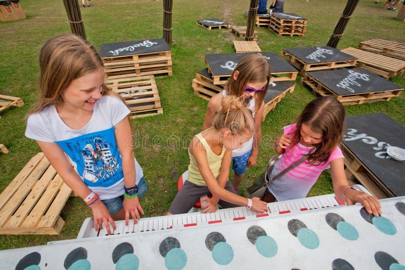 Piano del juego de las muchachas en el patio verde fotos de archivo libres de regalías