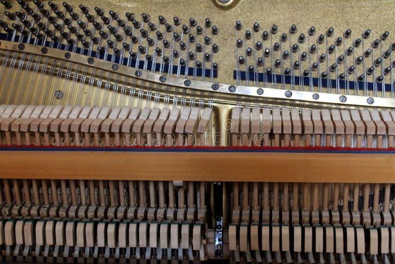 Piano dentro dos martelos de madeira das cordas e de outros detalhes musicais, esperando o piano mestre do afinador foto de stock royalty free