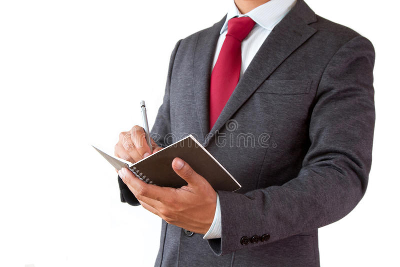 Piano di scrittura dell'uomo d'affari con la penna ed il blocco note fotografia stock