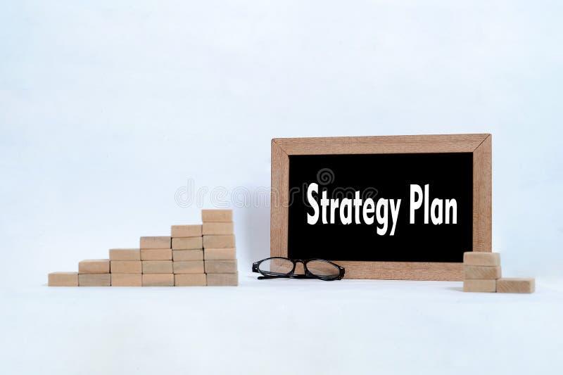 Piano di strategia scritto sulla lavagna Blocchetto legno di vetro dell'occhio e che impila come simbolo della scala di punto del fotografie stock