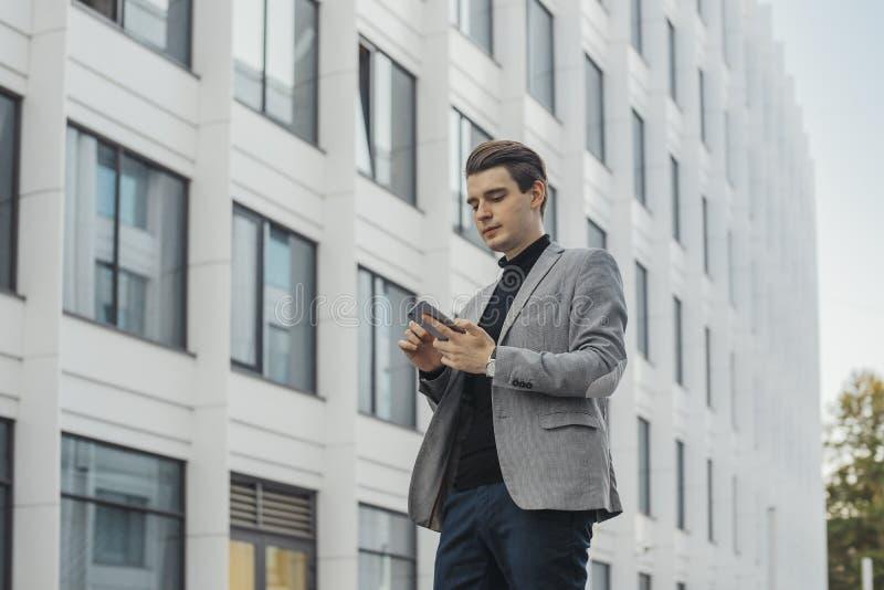 Piano distante di giovane uomo d'affari che parla dal telefono cellulare accanto al grattacielo fotografie stock