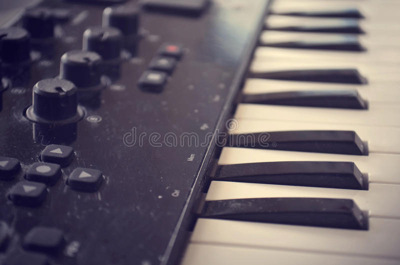 Piano or electone midi keyboard, electronic musical synthesizer white and black key. Vintage effect, instagram filter. Style. Close up royalty free stock image