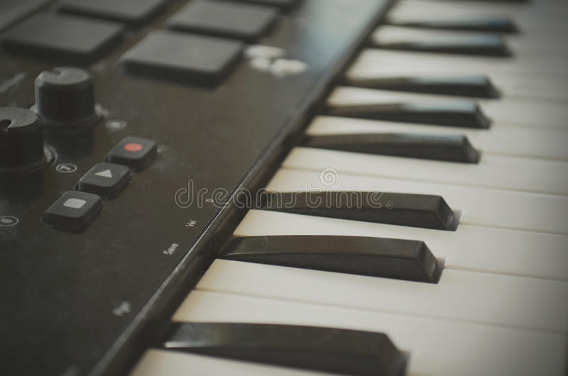 Piano or electone midi keyboard, electronic musical synthesizer white and black key. Vintage effect, instagram filter. Style. Close up stock photo